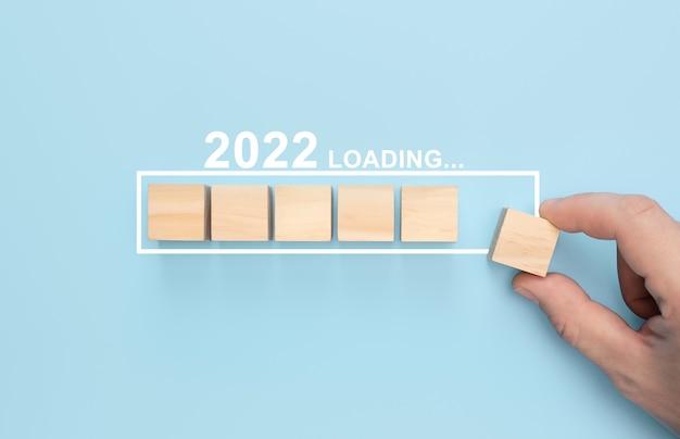 Carregando novo ano 2022 com a mão colocando cubo de madeira na barra de progresso carregando novo ano 2022