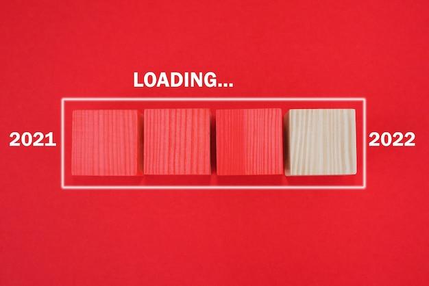 Carregando o ano novo 2022, comece o texto no cubo de madeira, pensando no conceito de objetivo. um novo começo. fundo vermelho.