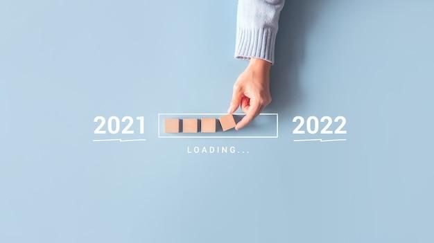 Carregando o ano novo de 2021 a 2022 com a barra de progresso colocando a mão no cubo