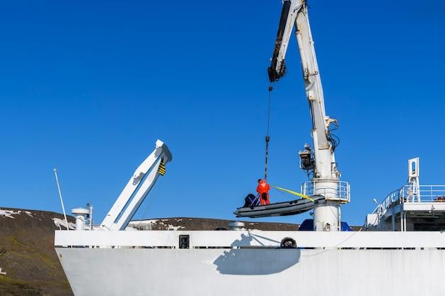 Carregando o barco inflável com o motorista no convés usando o guindaste do navio. expedição ao ártico.