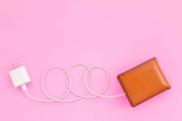 Carregando o poder para o conceito financeiro: vista superior do cabo branco do carregador conectado à carteira marrom