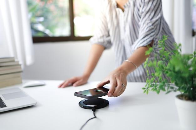 Carregar a bateria do celular com o dispositivo de carregamento sem fio na mesa. carregamento do smartphone em uma base de carregamento. telefone celular próximo ao carregador sem fio