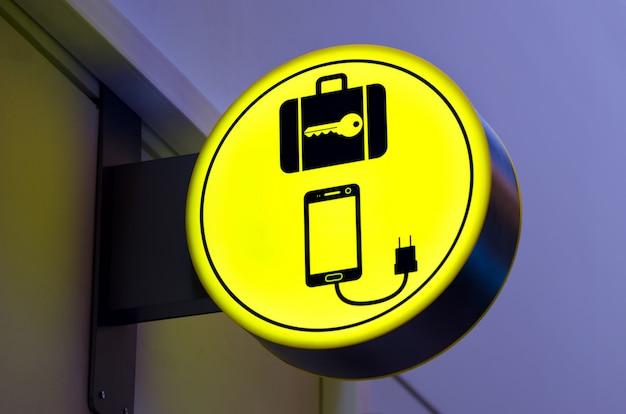 Carregar o celular, ícone de bateria de celular na área pública, aeroporto. sinal de bagagem do cacifo. espaço da cópia