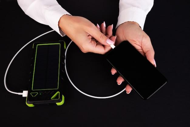 Carregar um smartphone usando um banco de energia em um fundo preto nas mãos de uma menina