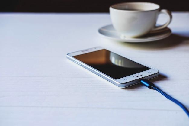 Carregue o celular em cima da mesa.