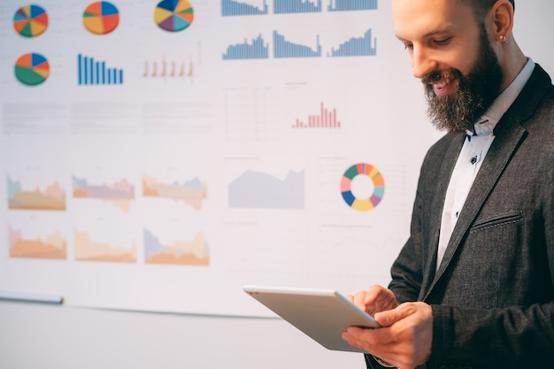 Carreira de sucesso. homem de negócios jovem executando a empresa. líder masculino de pé sobre o quadro branco desfocado com gráficos, sorrindo.