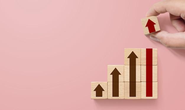 Carreira na escada para o conceito de processo de sucesso de crescimento de negócios. mão, organizar o bloco de madeira de empilhamento como degrau com a seta para cima