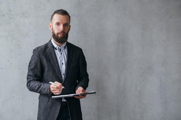 Carreira profissional de sucesso. homem de negócios jovem em pé com caneta e prancheta sobre fundo cinza. copie o espaço.
