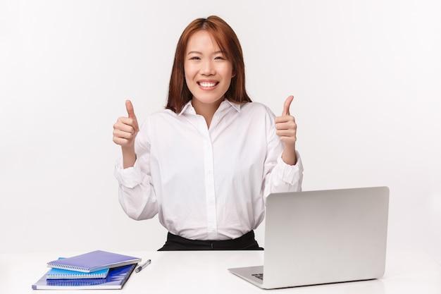 Carreira, trabalho e conceito de mulheres empresárias. o retrato do close-up da senhora asiática assegurada nova alegre do escritório aprova a ideia, garante a qualidade de serviço, senta-se na mesa com laptop e documentos