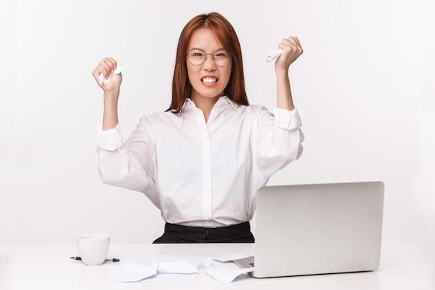 Carreira, trabalho e conceito de mulheres empresárias. retrato do close-up da senhora asiática incomodada irritada do escritório, gerente odeia a papelada, espreme documentos de raiva e aborrecimento, senta-se perto do laptop