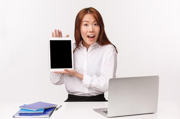 Carreira, trabalho e conceito de mulheres empresárias. retrato do close-up da senhora profissional jovem entusiasta do escritório, gerente, apresentando seu projeto no tablet, mostrando a tela na parede branca