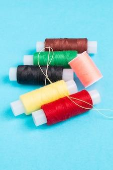 Carretéis coloridos de linha de costura em um fundo azul