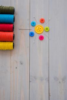 Carretéis coloridos do fio com agulhas decorativas; pinos e botões coloridos na mesa de madeira