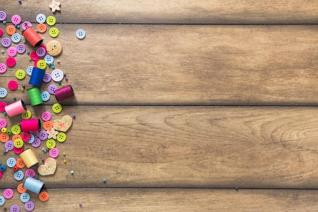 Carretéis coloridos e botões no cenário de madeira