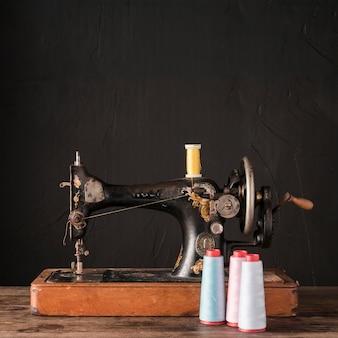 Carretéis com fio perto de máquina de costura antiga