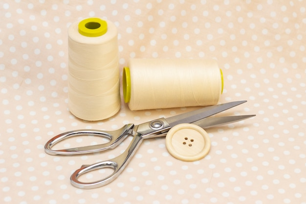 Carretéis de algodão bege. tesoura e um botão de madeira em um tecido de bolinhas bege. conceito de costura natural