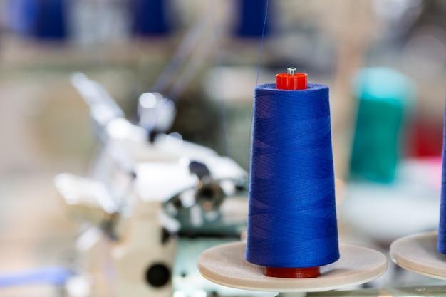 Carretéis de fios azuis na máquina de costura, fábrica