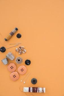Carretéis de linha; botões; agulha; dedal e botão em um pano de fundo laranja