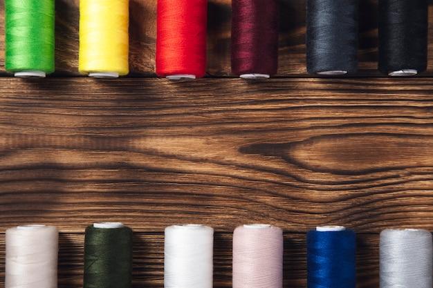 Carretéis de linha colorida na madeira.
