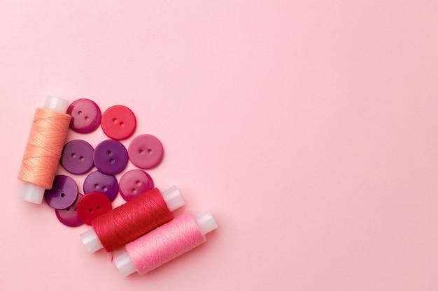 Carretéis de linha multicoloridos e botões em fundo rosa