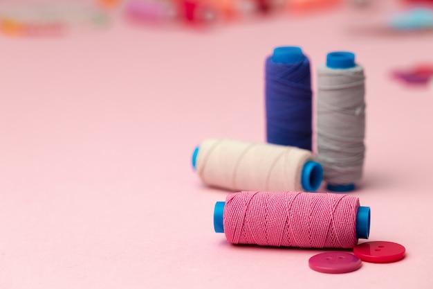 Carretéis de linha multicoloridos e botões em rosa