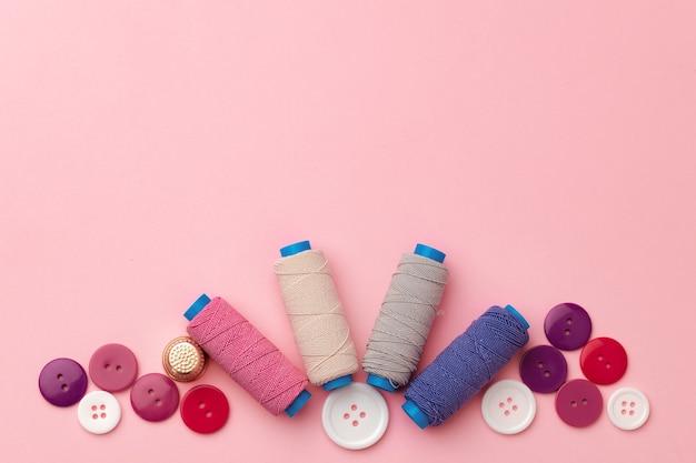 Carretéis de linha multicoloridos e botões na superfície rosa