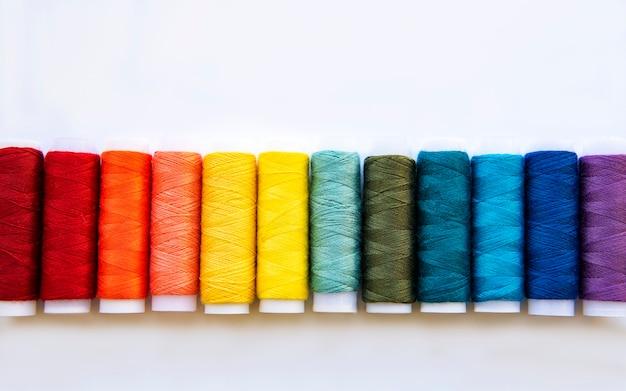 Carretéis de linha nas cores do arco-íris em um fundo branco, camada plana