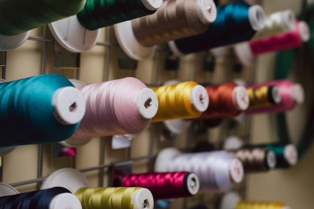 Carretéis de linha pendurada em uma alfaiataria. os novelos para a máquina de costura penduram em uma loja de costura.