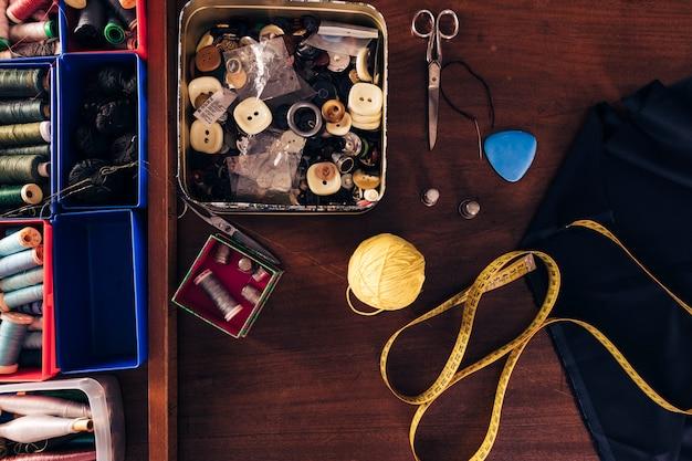 Carretéis de linhas de costura; botões; bola de lã; fita métrica; giz; tecido e tesoura na mesa de madeira