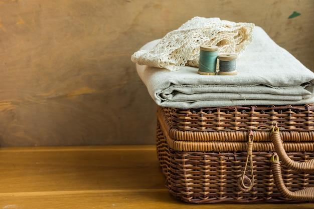 Carretéis de madeira vintage com linhas multicoloridas em tecido de linho dobrado, rendas de algodão na cesta de vime