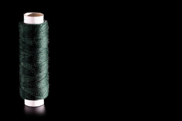 Carretel com fios de seda de costura verdes isolados em um fundo preto, close-up, espaço de cópia.