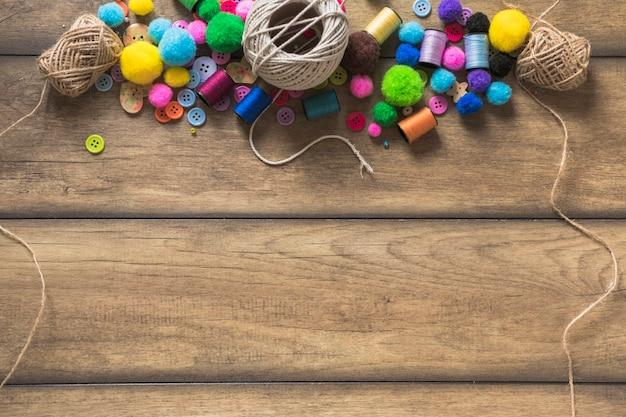 Carretel de corda; botões coloridos; carretel e bolas de algodão na prancha de madeira