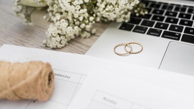Carretel de corda; computador portátil; anéis de casamento e flores de respiração do bebê