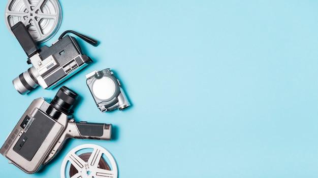 Carretel de filme e vários tipos de filmadora no fundo azul