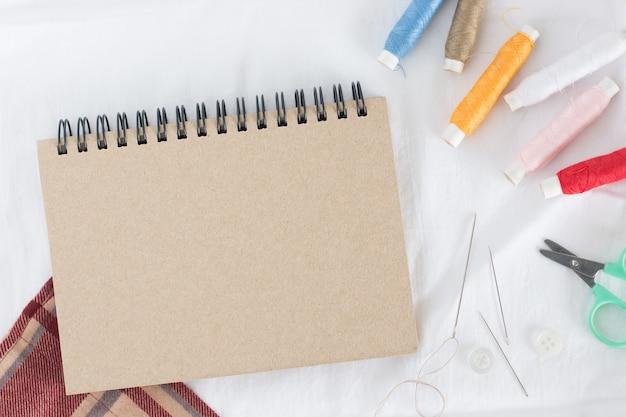 Carretel de fio muitas cores com agulha, pequena tesoura e caderno marrom em tecido branco