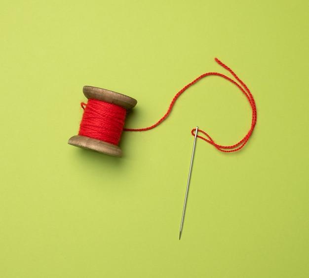 Carretel de madeira com fio de lã vermelha sobre fundo verde, vista superior