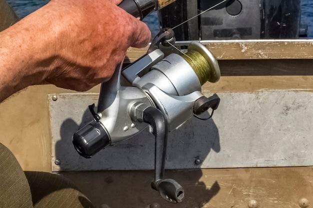 Carretel de pesca velho na mão de um pescador. copie o espaço. fechar-se