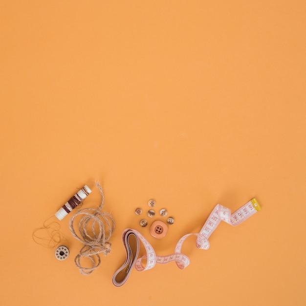 Carretel marrom; corda; botões e fita métrica em um pano de fundo laranja