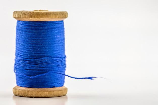 Carretel ou carretel da linha de costura azul isolada no branco.