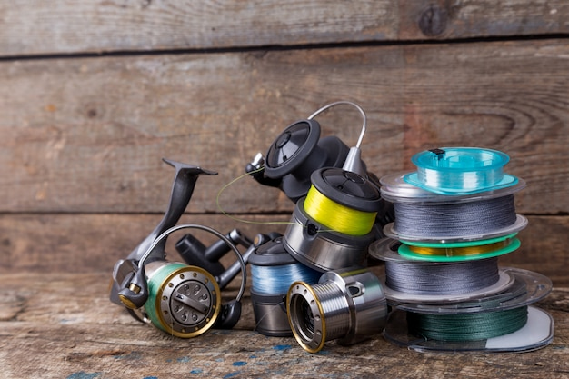 Carretilhas de pesca e spoole com linha na mesa de madeira