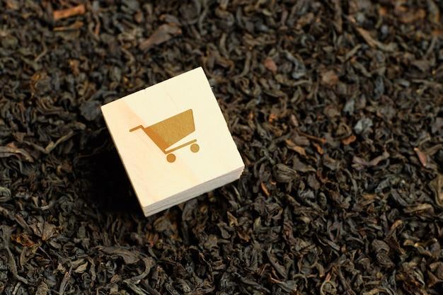 Carrinho abstrato em um cubo de madeira e em um chá preto seco. o conceito de aquisição de mercadorias.