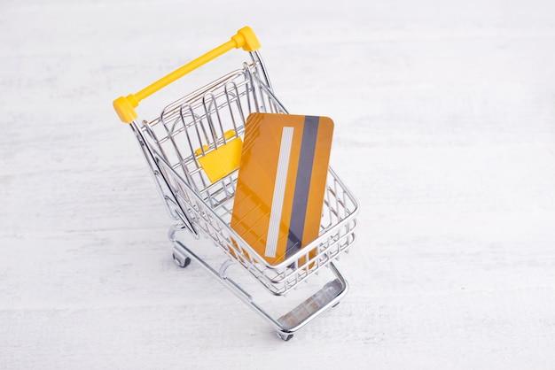 Carrinho amarelo com cartão de crédito, compras on-line conceito
