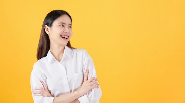 Carrinho asiático bonito alegre da mulher e braços cruzados
