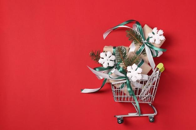 Carrinho carrinho com presentes de ano novo em papel kraft com fitas verdes e brancas na superfície vermelha.