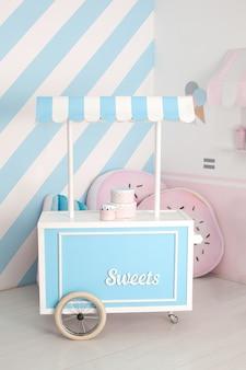 Carrinho com barra de chocolate. zona infantil com doces: pirulitos, sorvete e barra de chocolate.