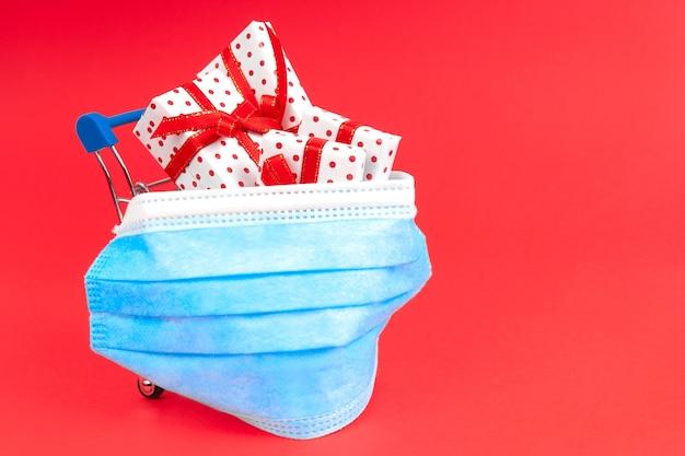 Carrinho com presentes em máscara protetora com copyspace. comprar presentes para o feriado durante o vírus
