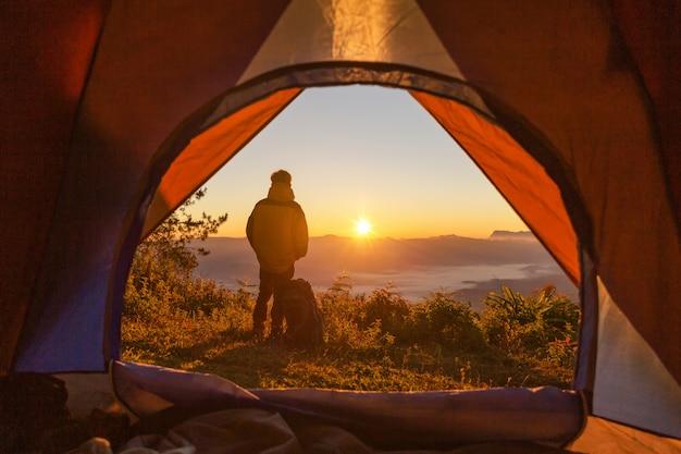 Carrinho de alpinista no acampamento perto de barraca laranja e mochila nas montanhas