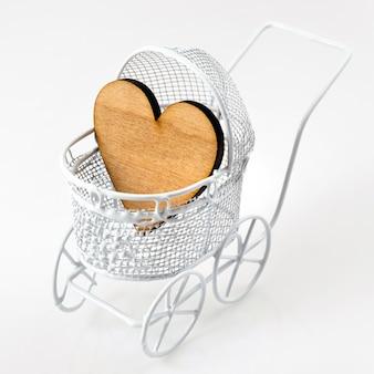 Carrinho de bebê com coração de madeira no fundo branco. cartão recém-nascido.
