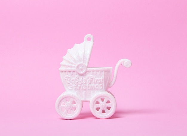 Carrinho de bebê de brinquedo branco sobre fundo rosa. espaço de cópia.
