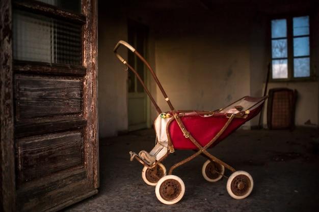 Carrinho de bebê enferrujado dentro de um prédio com portas e janelas gastas